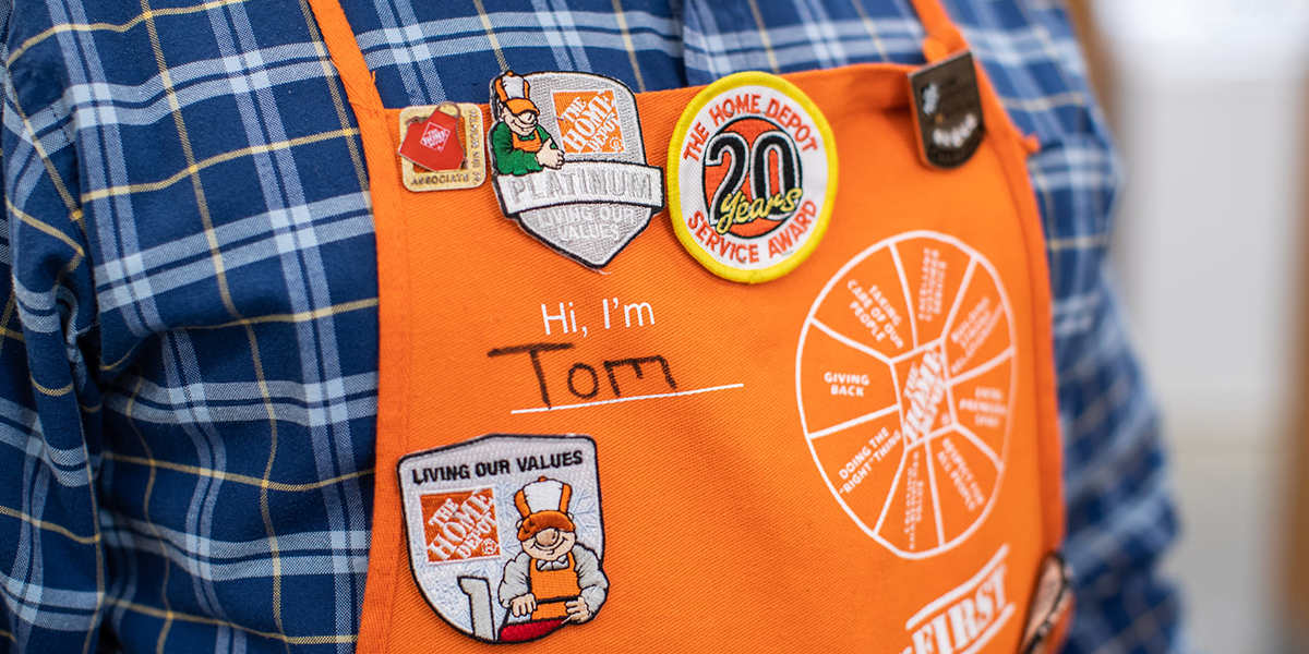 Close up of man's apron adorned with pins