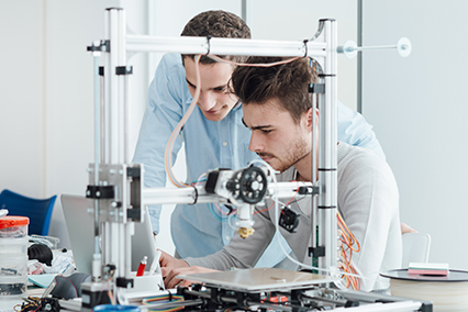 2 student researchers at a laptop behind metal device in laboratory