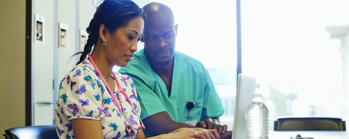 Medical professionals using laptop in meeting room