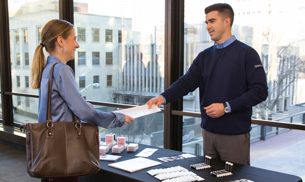 Travelers' recruiter hands career information to a job seeker at a hiring event