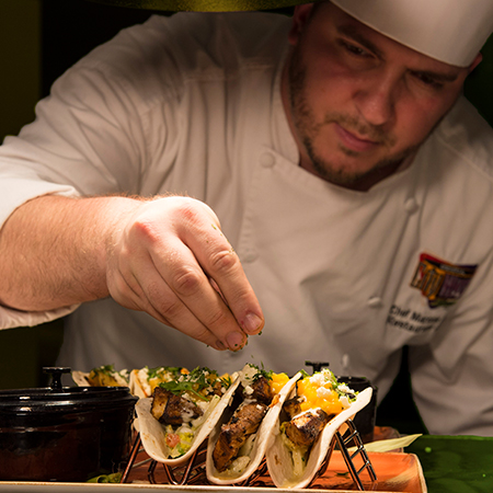 Culinary Team Member puts finishing touches on tacos