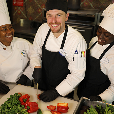 Group of three Culinary Team Members, one of whom is prepping brightly colored vegetables
