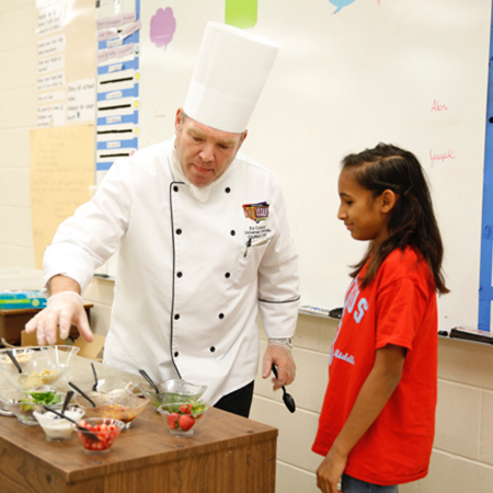 Chef at Universal Orlando Resort provides instruction to a student