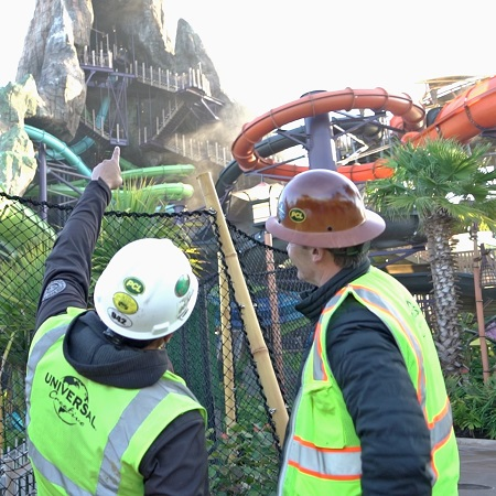 Two team members in construction hardhats looking up toward Volcano Bay