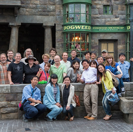 Group of Team members standing and kneeling in front of The Dogweed and Deathcap storefront in Hogsmeade at Universal Orlando Resort's The Wizarding World of Harry Potter