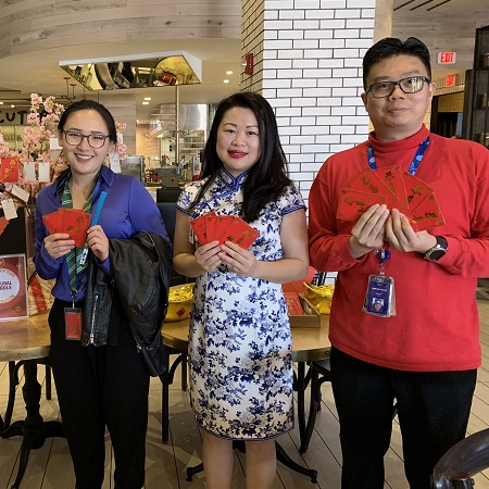 3 Asian Team Members holding red envelopes