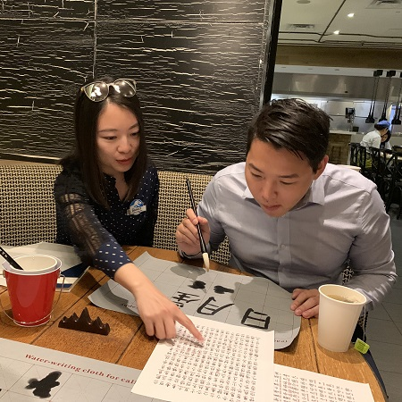 Two Team Members practicing Chinese calligraphy at Universal Orlando Resort's Lunar New Year Celebration event.