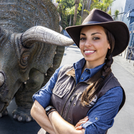 Woman in safari gear standing next to triceratops at Jurassic World - The Ride
