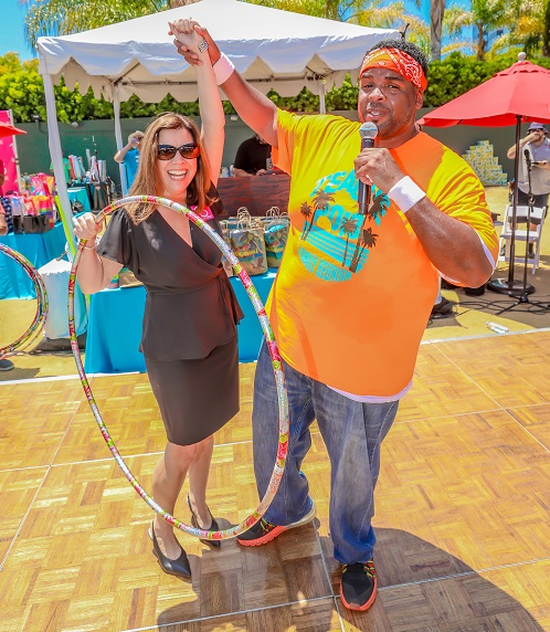 USH Team Member holding up the hand of a guest holding a hula hoop