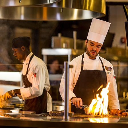 Culinary Team Member prepares an impressive flambe dish