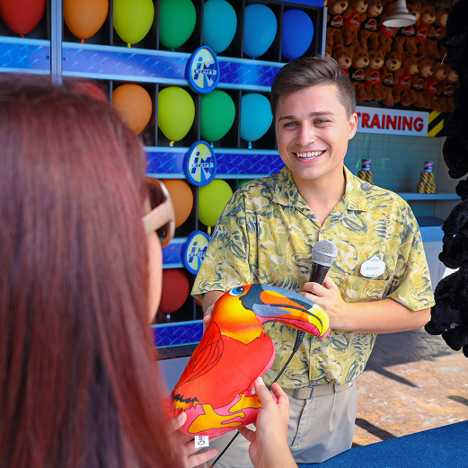 Team Member engages with guest who has just won a toucan bird prize at one of Universal Orlando Resort's many games of chance