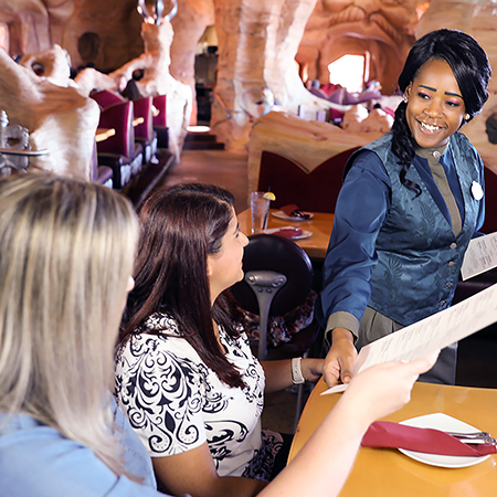Team Member greets guests and hands out menus at one of Universal Orlando Resort's unique restaurant venues