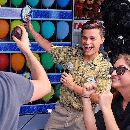 Team Member cheers on guest who is trying his hand popping balloons at one of Universal Orlando's many game kiosks
