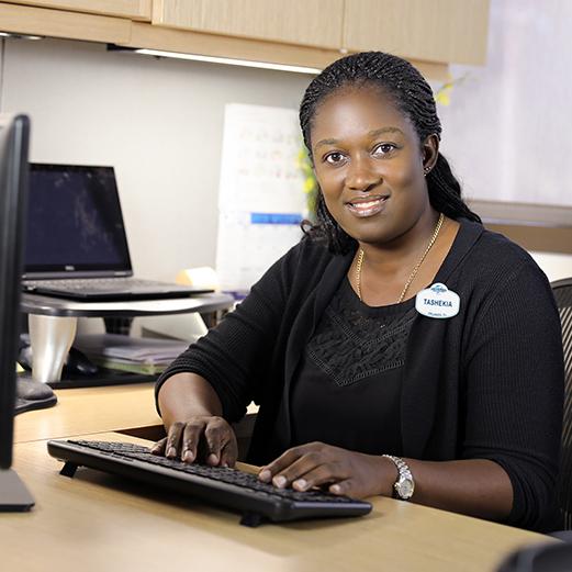 Female Team Member in Finance sits at desk using computer keyboard