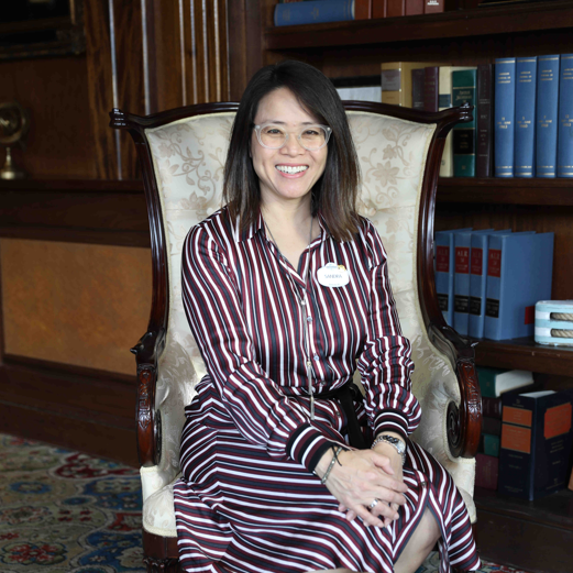 Administration team member seated in a chair with library of books behind her