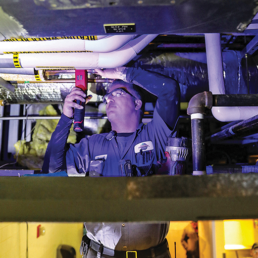 Facilities Team Member inspects piping for optimum operational performance