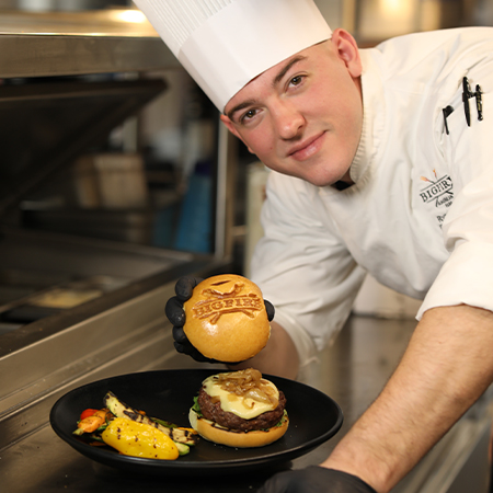 Chef holding a hamburger bun with the Bigfire logo toasted onto the top of it