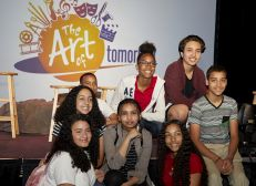 Group of students on a stage with 'The Art of Tomorrow' in the backdrop.