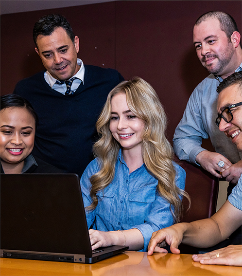 Five professional team members sitting around a laptop