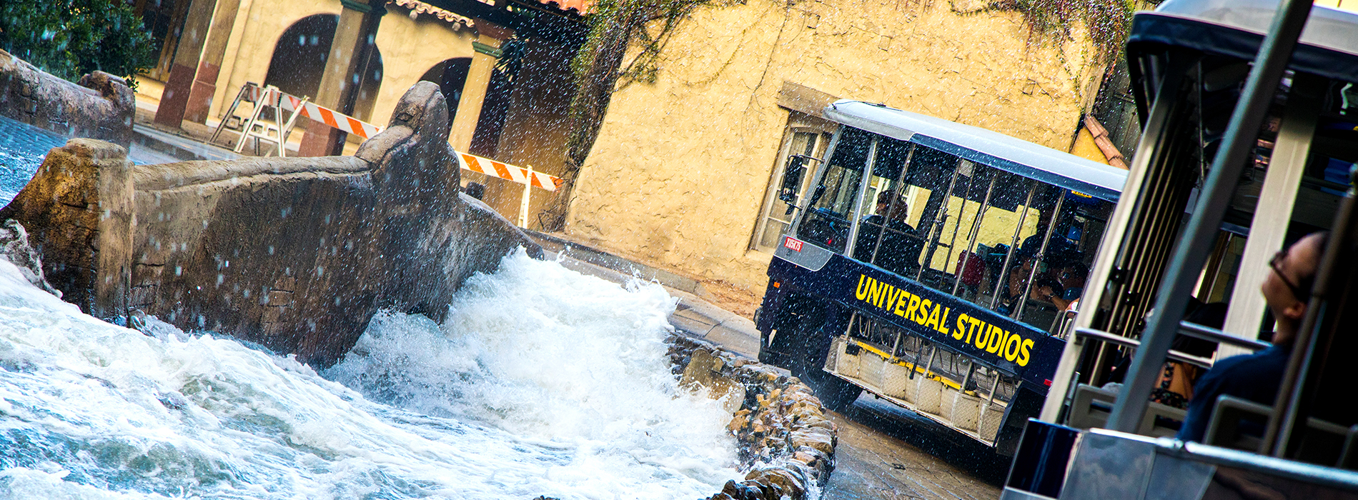Universal Studios tram driving alongside crashing waves of water.