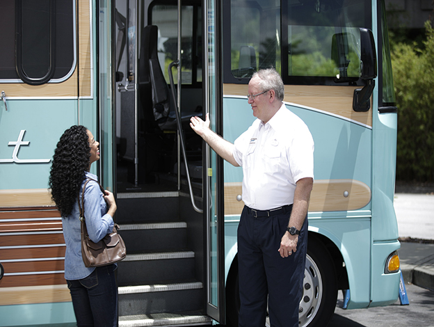Bus driver welcoming a woman