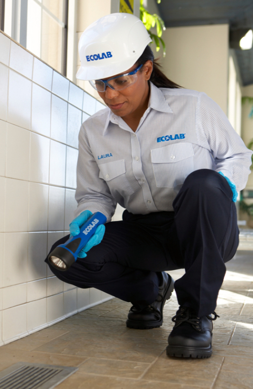 Ecolab employee searches for pests with a flashlight