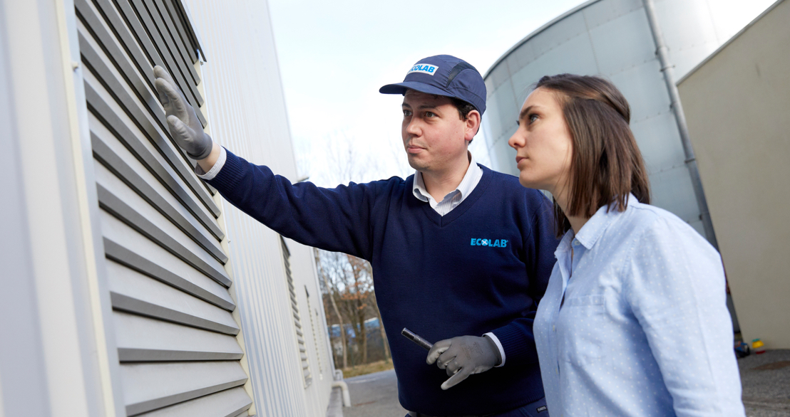 two Ecolab employees inspect a ventilation panel