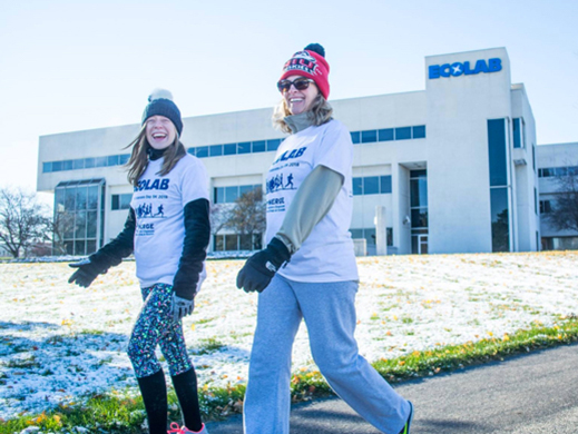 two smiling female employees exercise during winter weather on Ecolab's campus