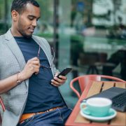 Man sitting in coffee shop and using phone