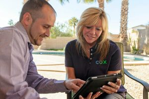 Femal Cox Salesperson reviewing a contract on a tablet with a male customer