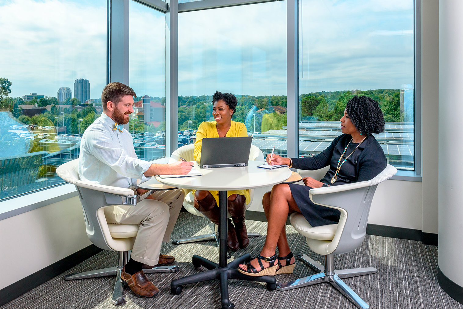 3 people talking around a meeting table in front of large windows