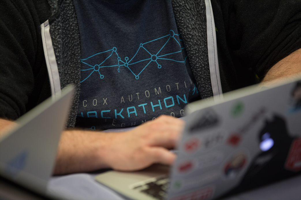 Person typing on laptop at Cox Automotive Hackathon photo