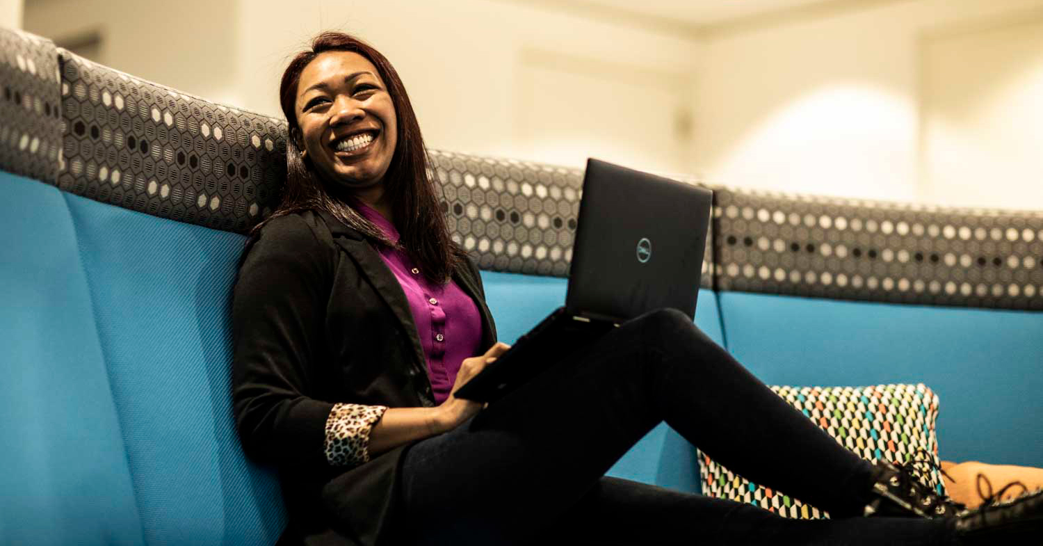 Photo of Jackie, smiling on a blue couch with a laptop.