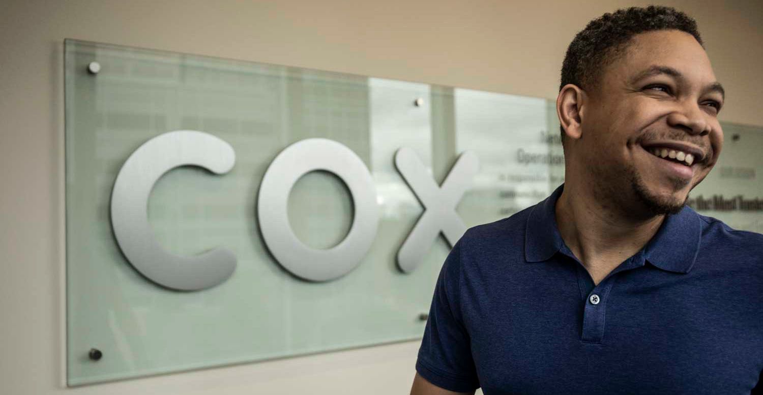 Photo of Kevin smiling in front of the Cox logo