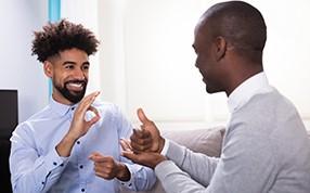 Dois homens afro-americanos se comunicando com a língua de sinais