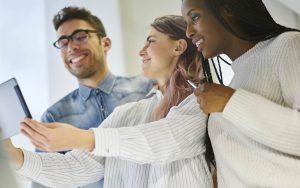 Grupo de três funcionários, sorrindo e colaborando no trabalho