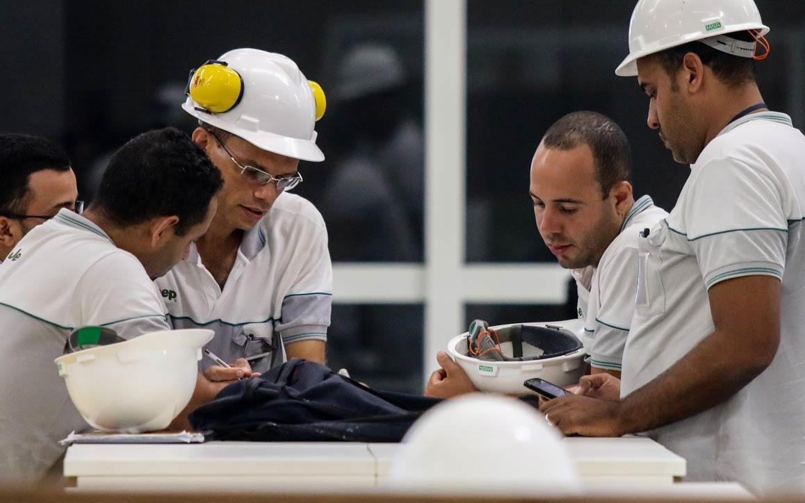 Grupo de trabalhadores com capacete de segurança envolvidos na resolução colaborativa de problemas