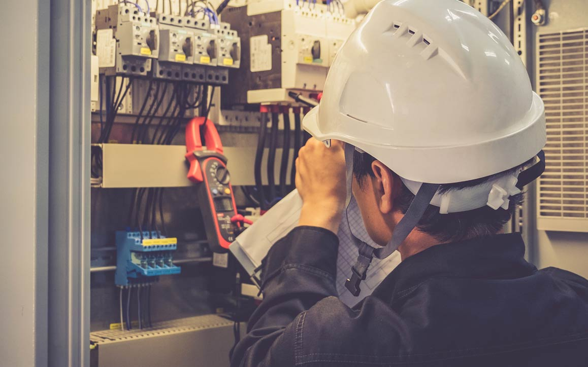 Funcionário usando capacete de segurança examinando controles eletrônicos