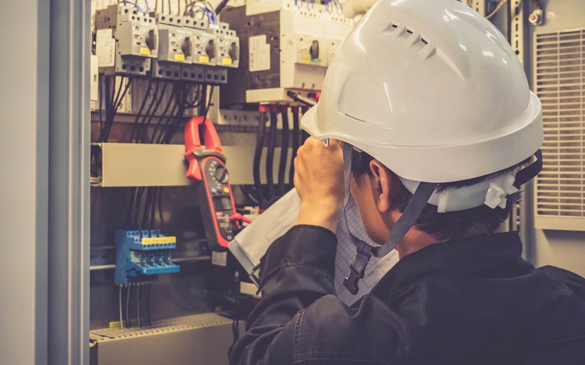 전자 제어 장치를 검사하는, 안전모를 쓴 직원