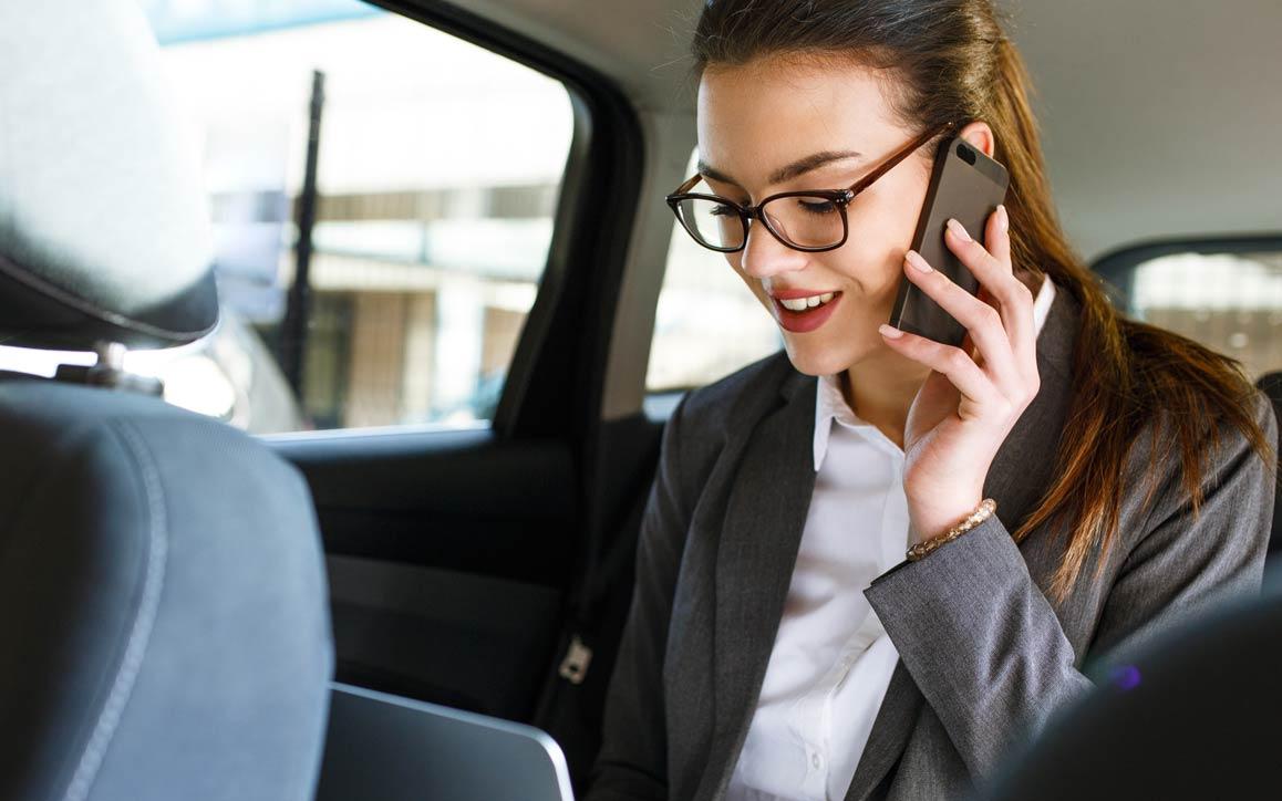 자동차 뒷좌석에서 전화하는 여성