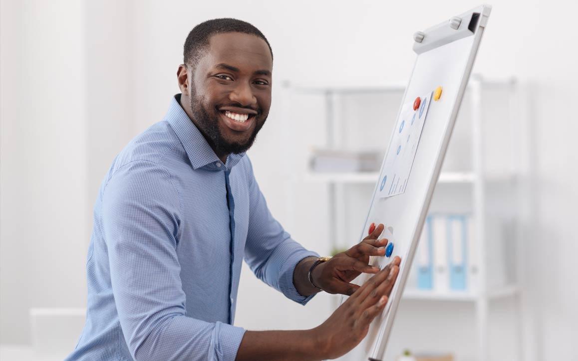 Homem em ambiente de escritório, trabalhando no quadro branco