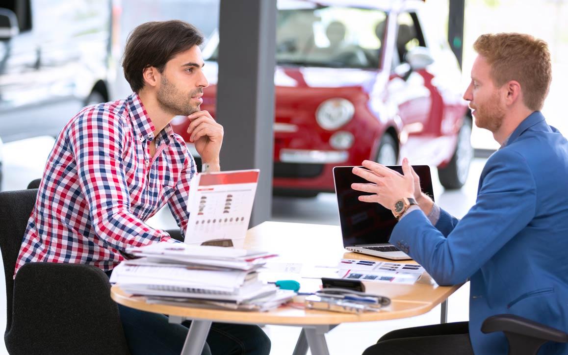 Funcionário e cliente em um showroom de carros