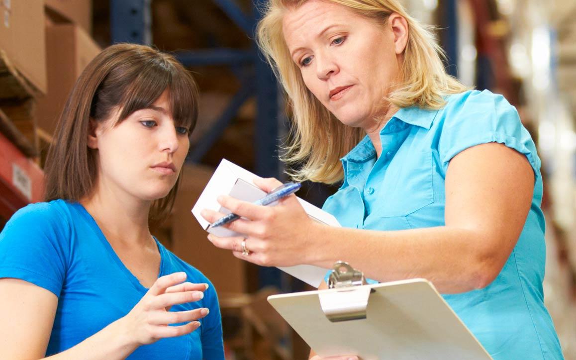 창고에서 부품을 확인하는 두 여직원