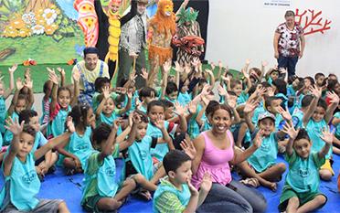 터키석 파란색 티셔츠를 입고 손을 들고 흔드는 많은 어린이들