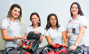 FCA가 기증한 안전벨트와 자동차 패브릭 트리밍으로 만든 핸드백을 전시하는 여성 넷.