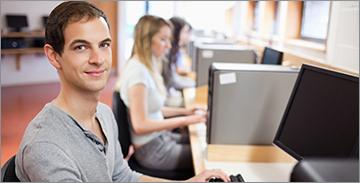 앞에서 컴퓨터로 작업하는 남학생