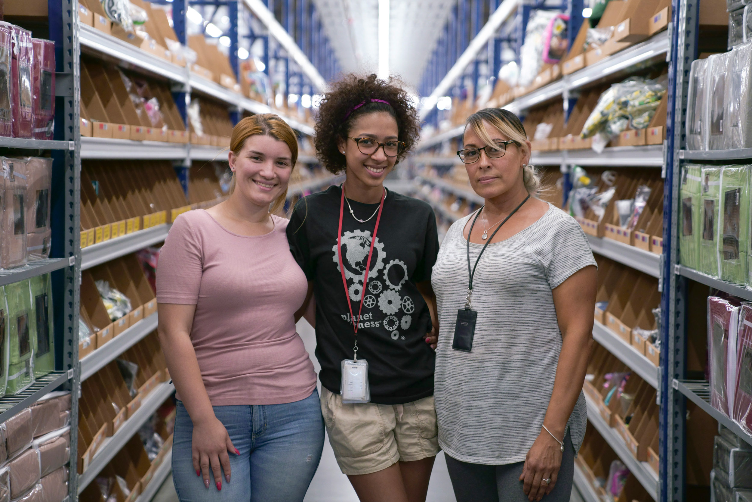 Zulily Team Members in a fulfillment center aisle.