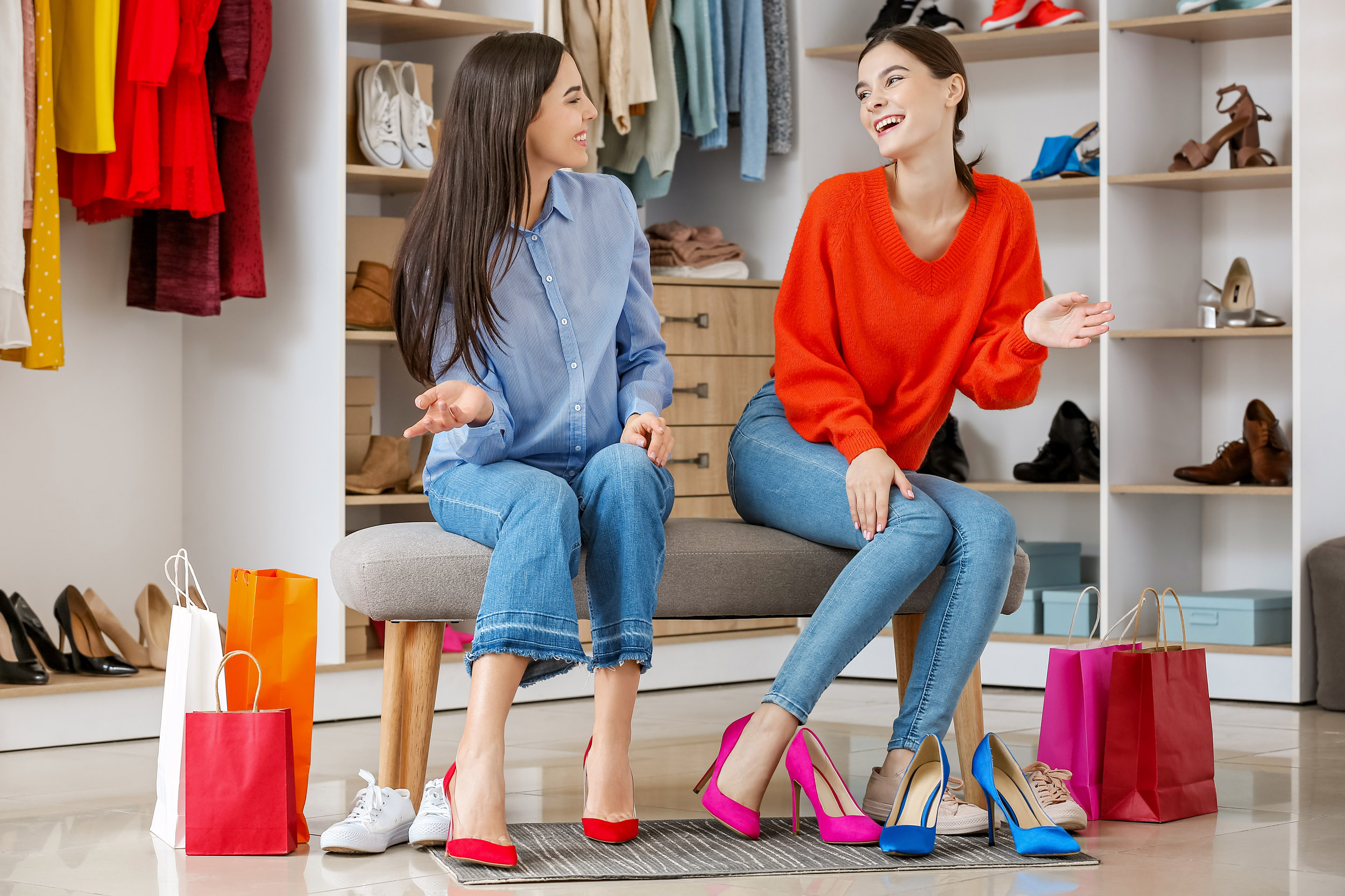Young women choosing shoes in modern store