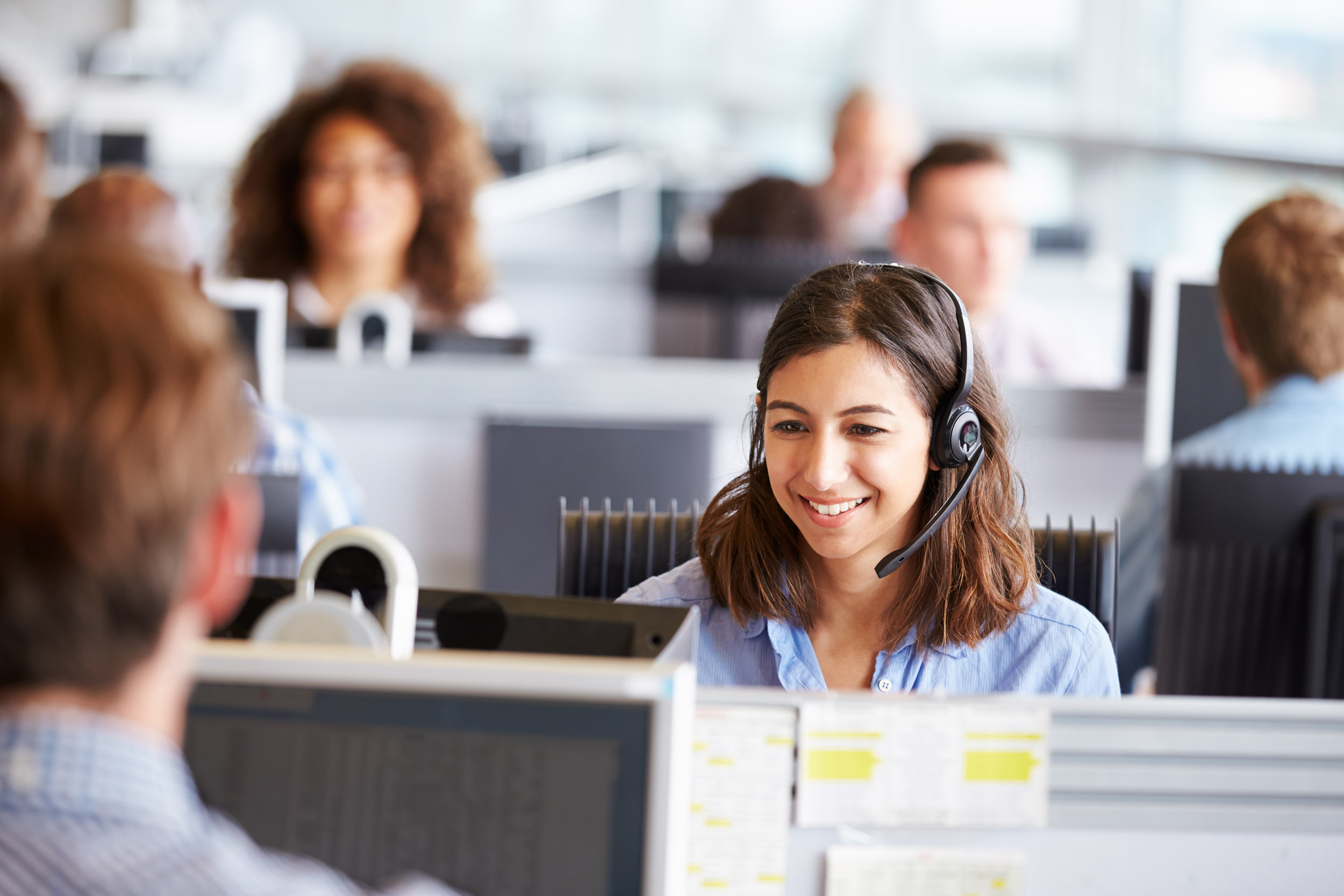 Young woman working in call centre, surrounded by colleagues.