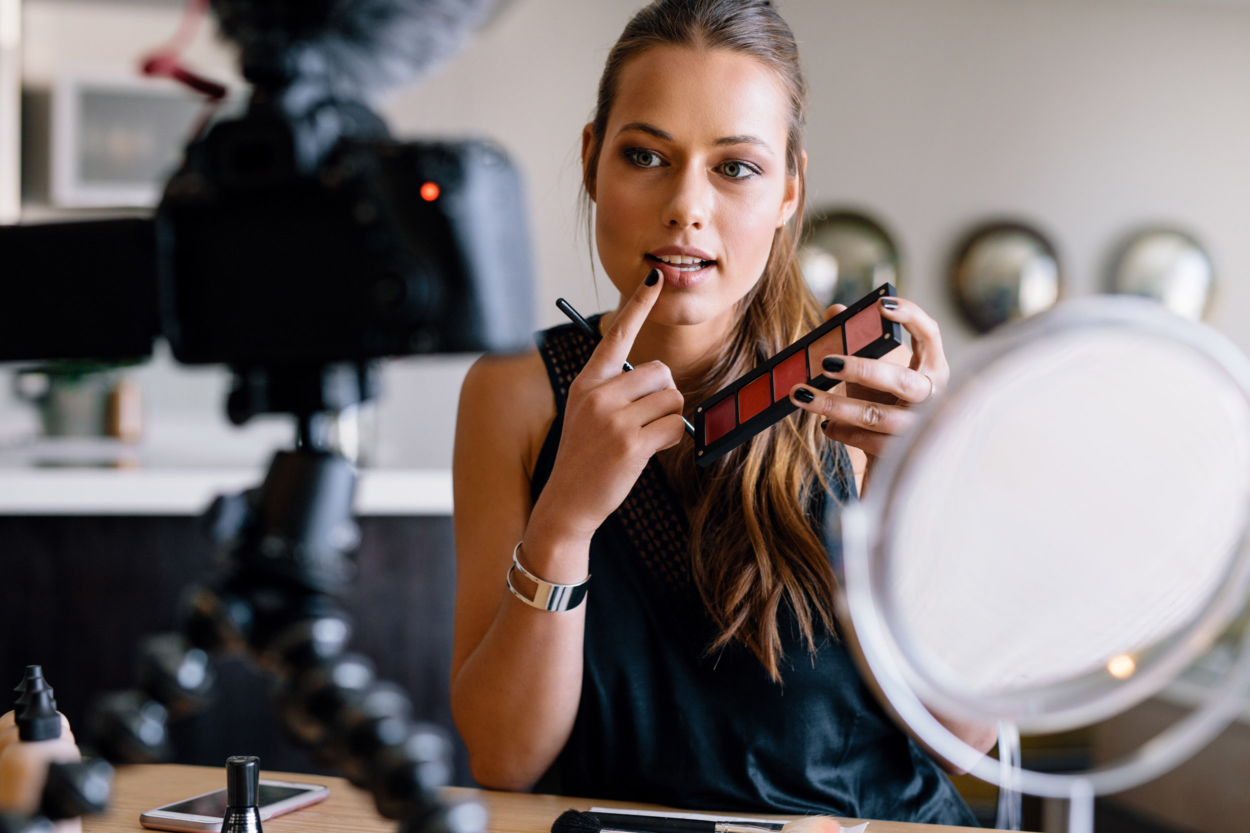 Young lady talking on cosmetics holding a makeup palette while recording her video. Woman making a video for her blog on cosmetics.